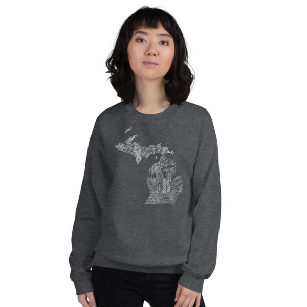 woman wearing a dark grey long sleeve sweatshirt with a white line drawing of the state of michigan design