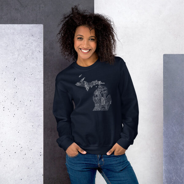 woman wearing a navy blue long sleeve sweatshirt with a white line drawing of the state of michigan design
