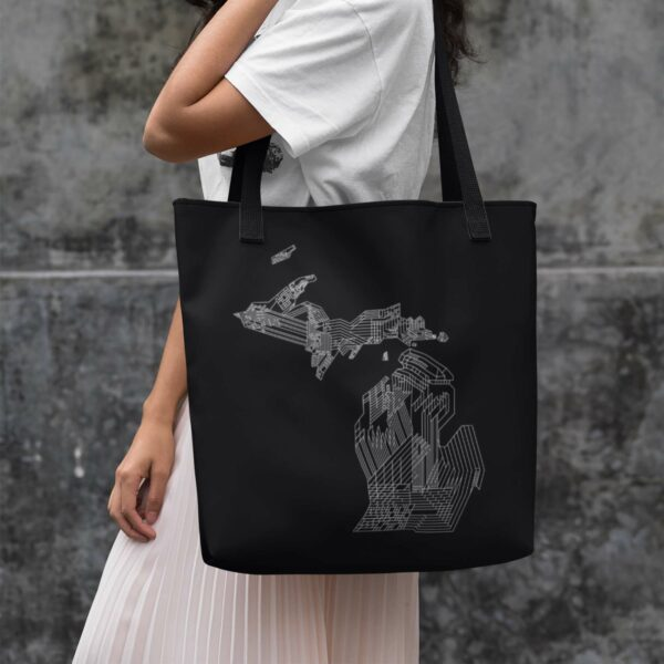 woman holding a black tote bag with black handles and white line drawing of the state of michigan