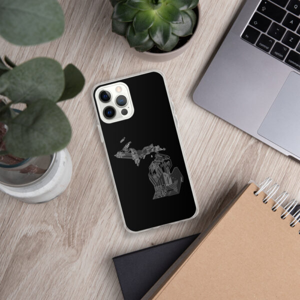 iphone case with a white line drawing of the state of michigan on a black background sitting next to a laptop