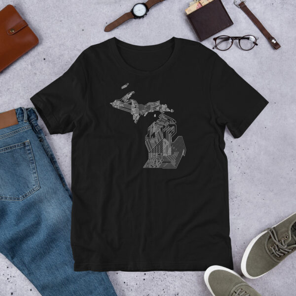 black short sleeve t-shirt with a white line drawing of the state of michigan design laying on a table with other accessories