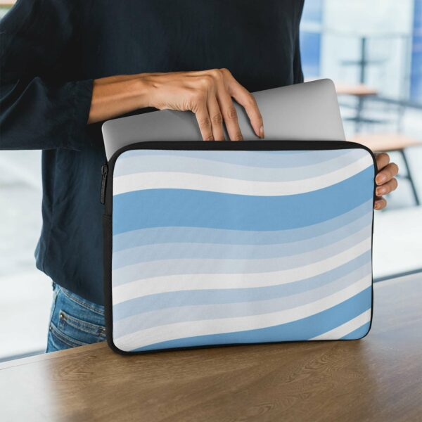 person holding a laptop sleeve with blue and white wavy lines