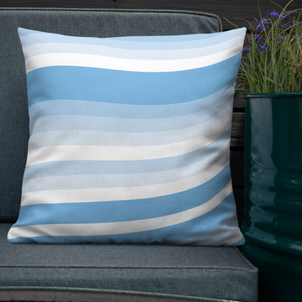 square pillow with a blue and white wavy line cirrus cloud design sitting on a chair next to a plant