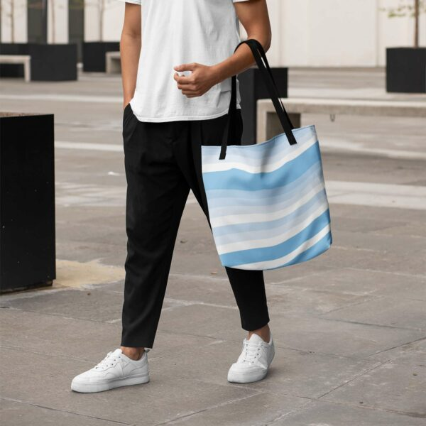 person holding a tote bag with black handles and a blue and white wavy cirrus cloud design