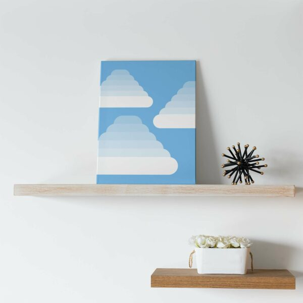vertical stretched canvas art print of three fluffy white cumulus clouds on a blue background sitting on a shelf