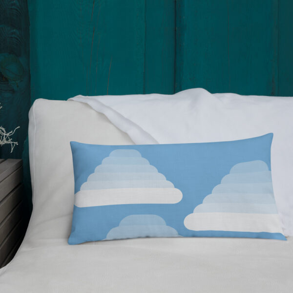 rectangle pillow with three white fluffy cumulus clouds on a blue background sitting on a sofa