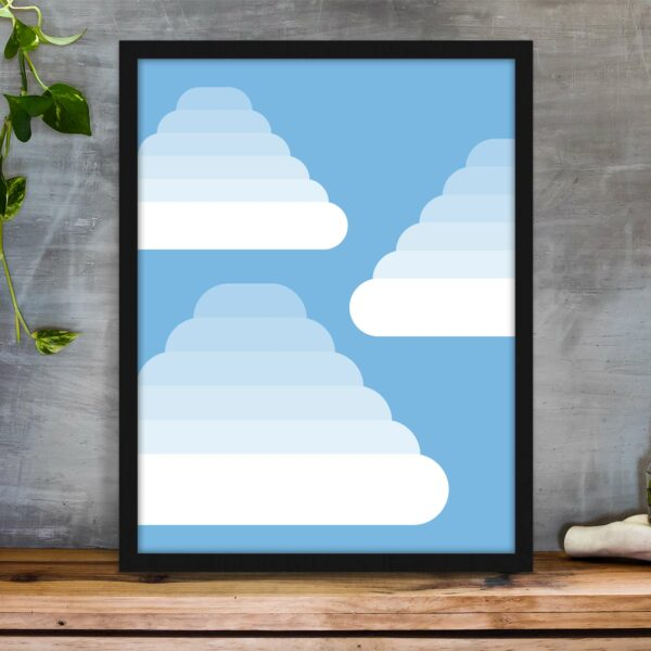 vertical fine art print of three fluffy white clouds on a blue background in a black frame on a table