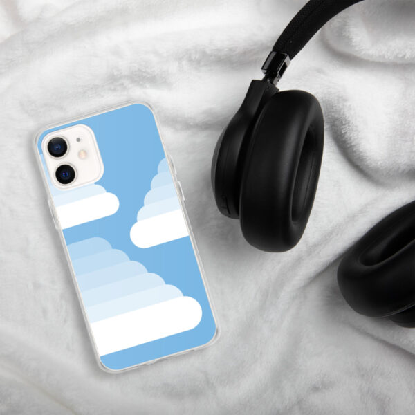 iphone case with three fluffy white cumulus clouds on a blue background sitting next to headphones