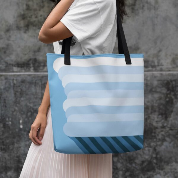 woman holding a light blue tote bag with black handles and a minimalist design of a tall white nimbus rain cloud