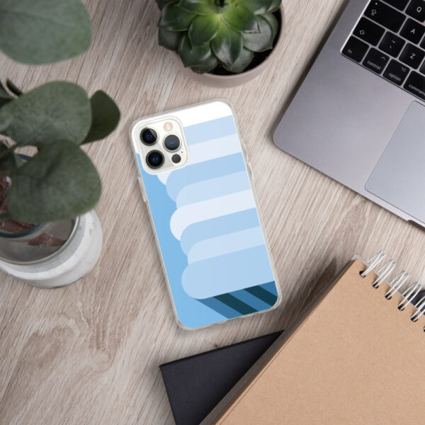 iphone case with a tall white nimbus rain cloud on a blue background sitting next to a laptop