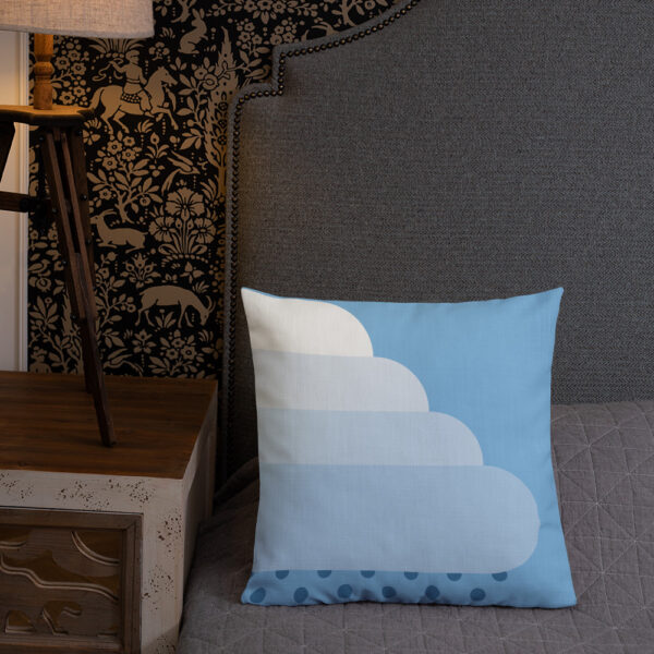 square pillow with a white cloud with raindrops on a blue background sitting on a bed