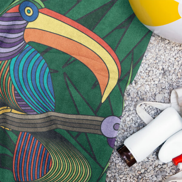 beach towel with a colorful toucan design next to a water bottle