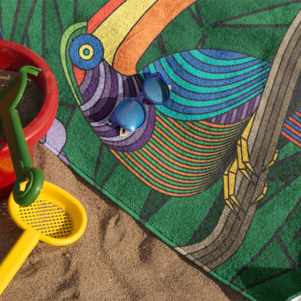 beach towel with a colorful toucan design on sand with sunglasses