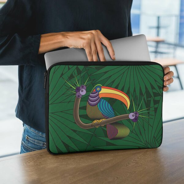 person holding a laptop sleeve with a colorful toucan design in front of a green leaf background