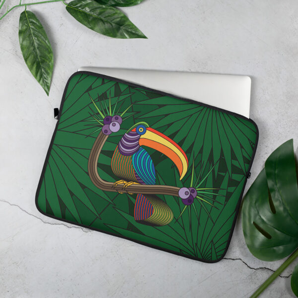laptop sleeve with a colorful toucan design in front of a green leaf background sitting on a table
