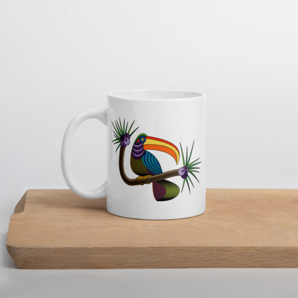11 ounce white ceramic coffee mug with a colorful toucan design on the side sitting on a cutting board