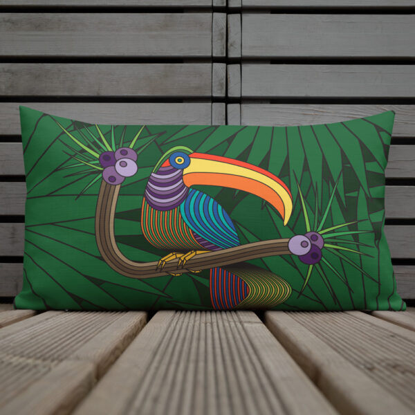 rectangle pillow with a colorful toucan design with a green leaf background sitting on a deck