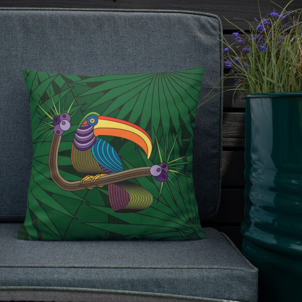 square pillow with a colorful toucan design with a green leaf background sitting on a chair next to a plant
