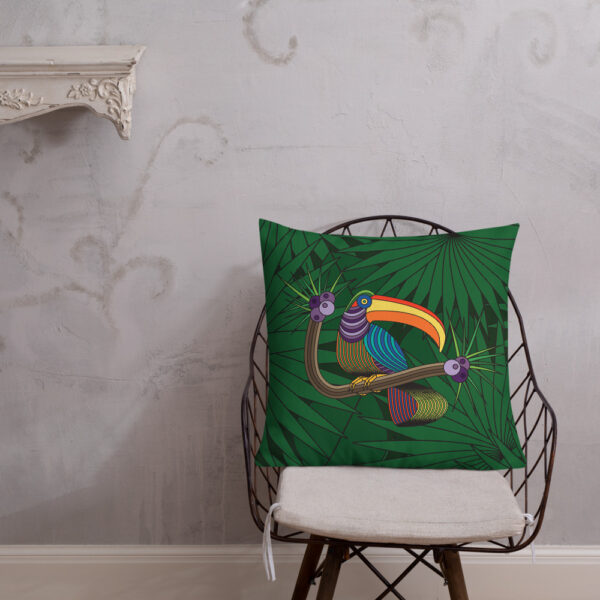 square pillow with a colorful toucan design with a green leaf background sitting on a chair