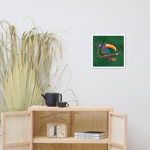 square fine art print of a colorful toucan with a green leaf background in a white frame hanging on a wall