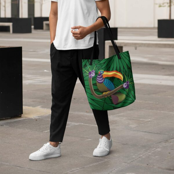 person holding a tote bag with black handles and a colorful design of a toucan in a rainforest