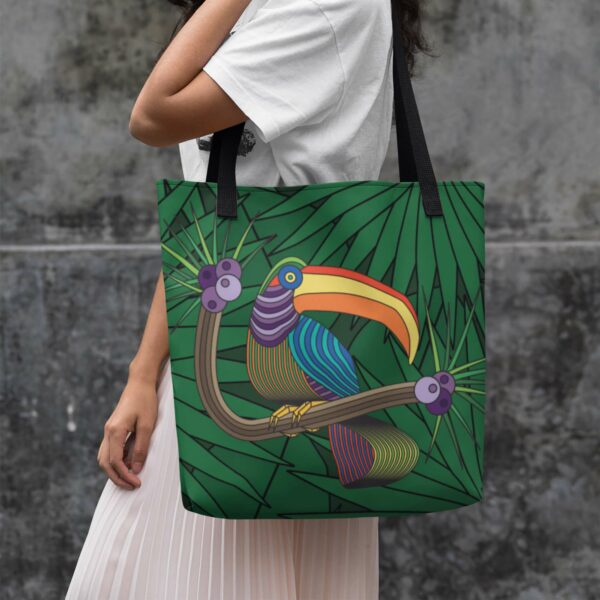 woman holding a tote bag with black handles and a colorful design of a toucan in a rainforest