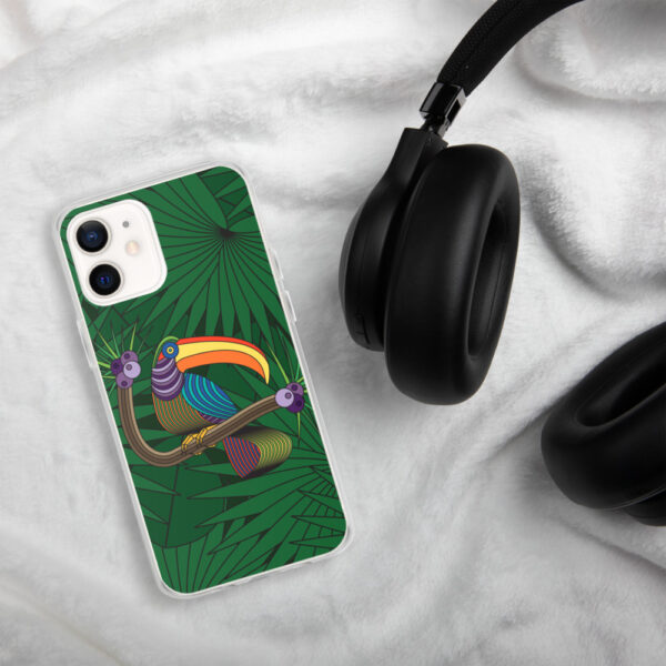 iphone case with a colorful design of a toucan in front of green leaves, sitting next to headphones