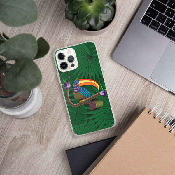 iphone case with a colorful design of a toucan in front of green leaves, sitting next to a laptop