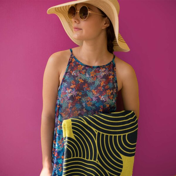 woman holding a yellow beach towel with an abstract black circle design