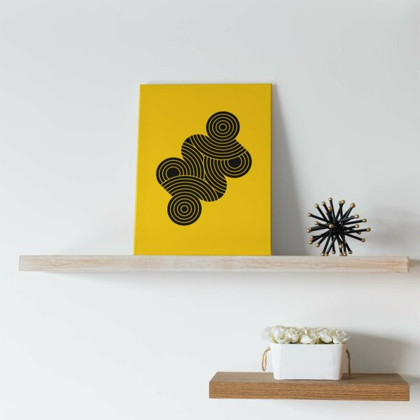 vertical stretched canvas art print with an abstract group of black circles on a yellow background sitting on a shelf