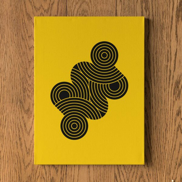 vertical stretched canvas art print with an abstract group of black circles on a yellow background hanging on a wall