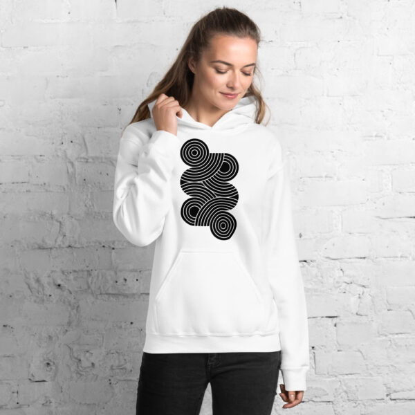 woman wearing a white hooded sweatshirt with an abstract design of black circles on the chest