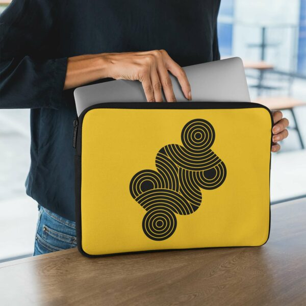 person holding a laptop sleeve with an abstract design of black circles on a yellow background