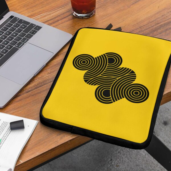 laptop sleeve with an abstract design of black circles on a yellow background sitting on a desk