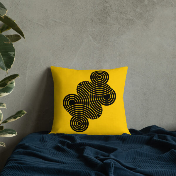 square pillow with an abstract design of black circles on a yellow background sitting on a bed