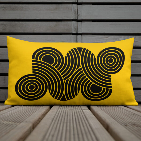 rectangle pillow with an abstract design of black circles on a yellow background sitting on a deck