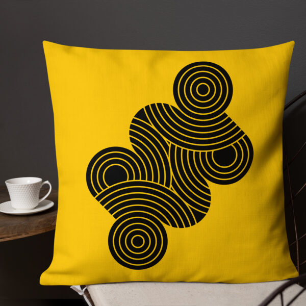 square pillow with an abstract design of black circles on a yellow background sitting on a chair next to a cup of coffee