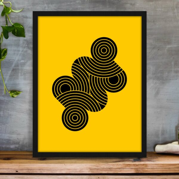 vertical fine art print with an abstract design of black circle shapes on a yellow background in a black frame on a table