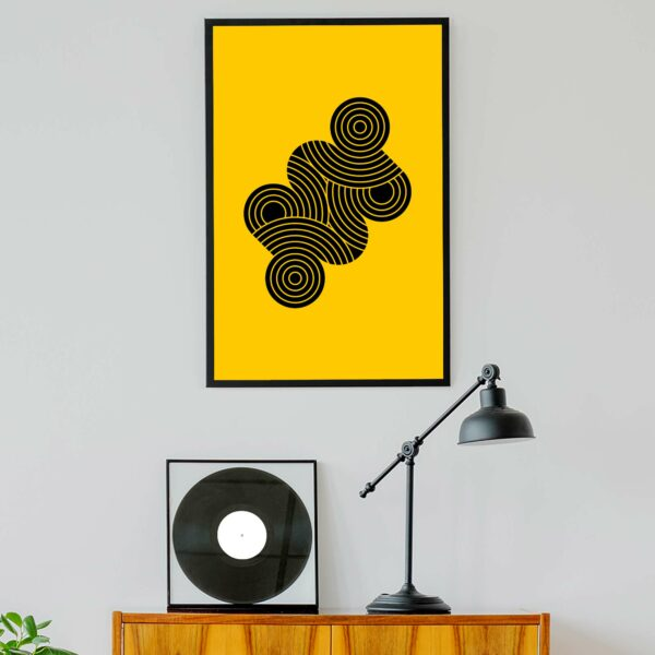 vertical fine art print with an abstract design of black circle shapes on a yellow background in a black frame hanging on a wall