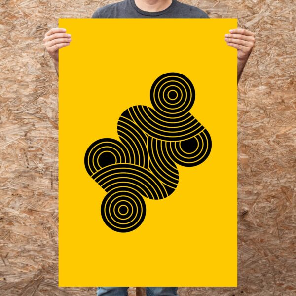 person holding a large vertical fine art print with an abstract design of black circle shapes on a yellow background