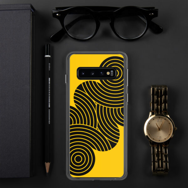 samsung phone case with an abstract design of black circles on a yellow background sitting next to a watch