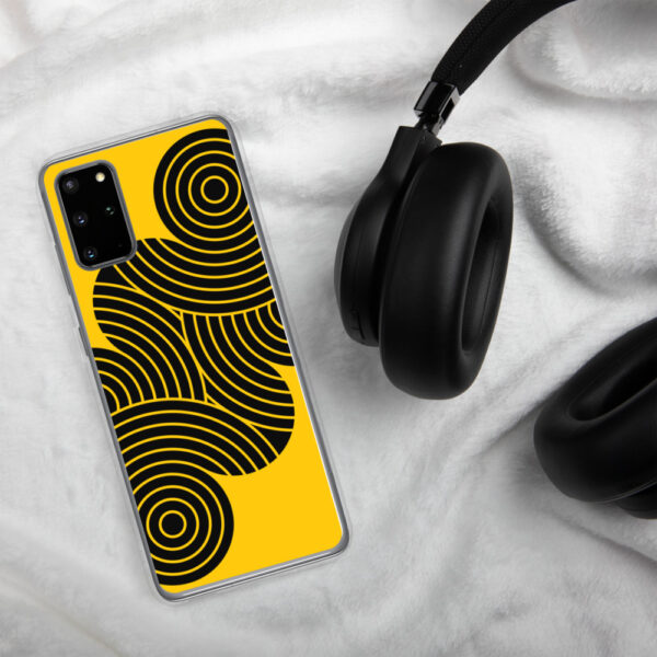 samsung phone case with an abstract design of black circles on a yellow background sitting next to headphones