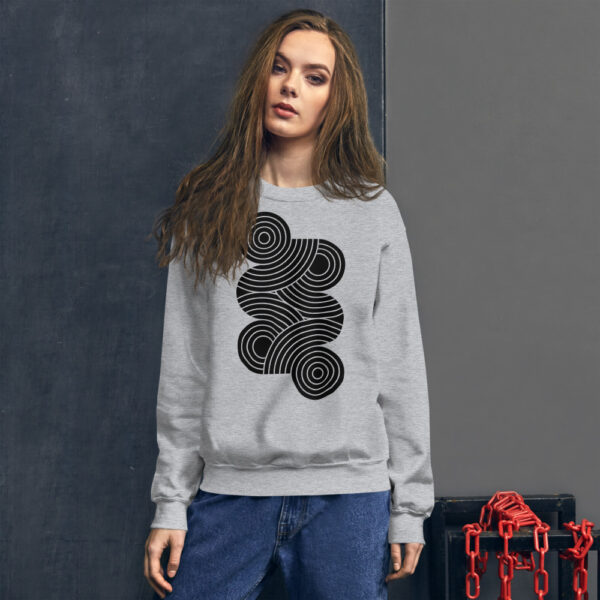 woman wearing a light grey long sleeve sweatshirt with an abstract group of black circles design