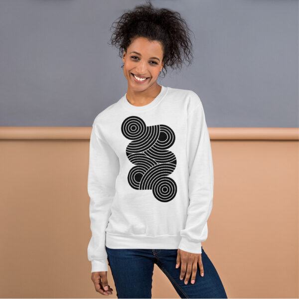 woman wearing a white long sleeve sweatshirt with an abstract group of black circles design