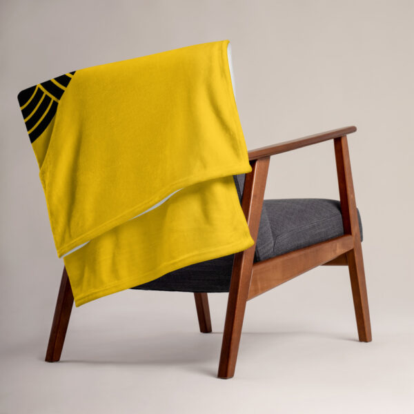 blanket with an abstract group of black circles on a yellow background, draped over a chair