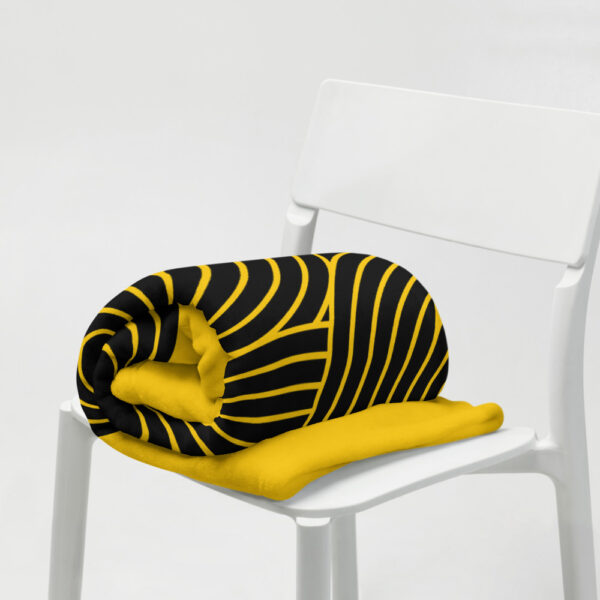 blanket with an abstract group of black circles on a yellow background, rolled up on a chair