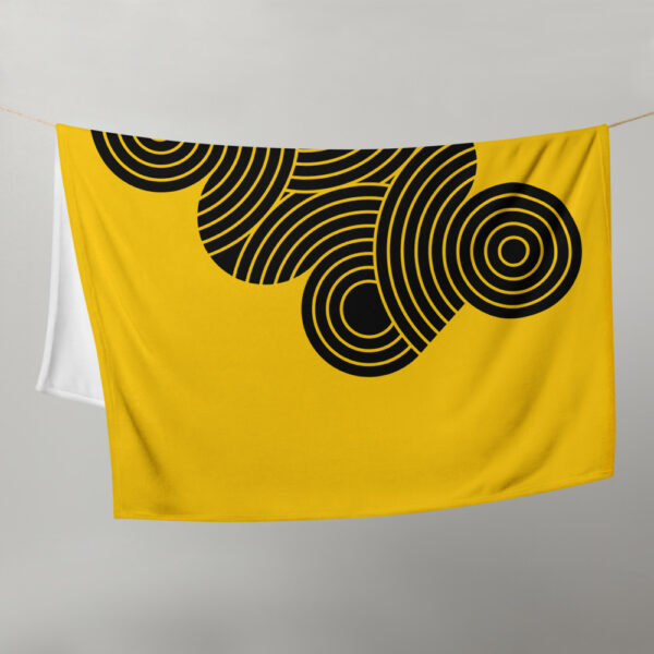 blanket with an abstract group of black circles on a yellow background, hanging on a clothes line