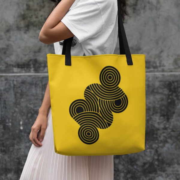 woman holding a yellow tote bag with black handles and an abstract design of black circles