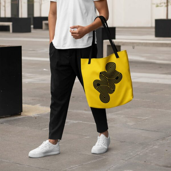 person holding a yellow tote bag with black handles and an abstract design of black circles