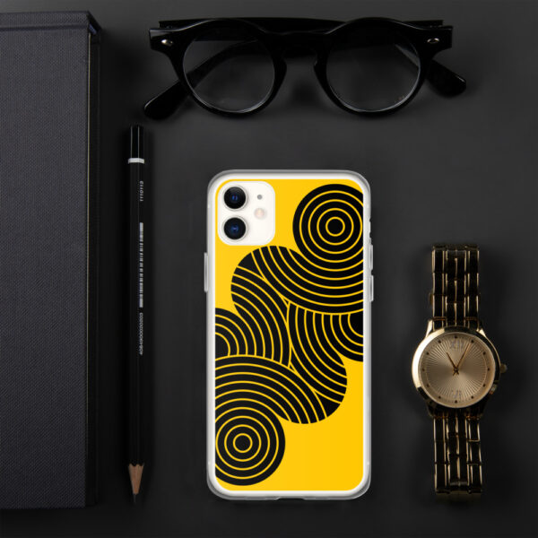 iphone case with an abstract design of black circles on a yellow background sitting next to a watch